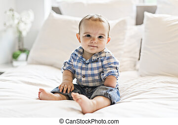 Adorable baby boy in white bedroom in morning