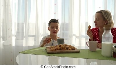 An adorable cute caucasian boy is eating cookie beside his...