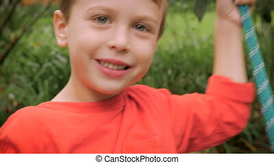 An adorable little boy swinging on a swing outside in slowmo...