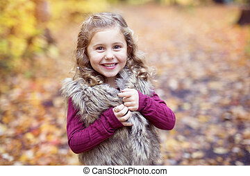 Adorable little girl in a autumn forest