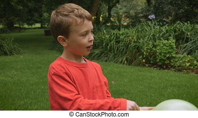 An adorable redhead boy playing outside pauses to talk about...