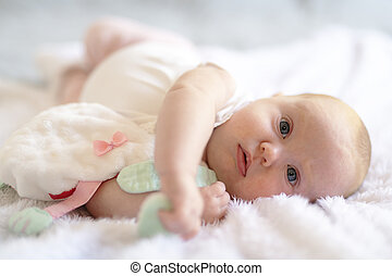 Adorable two months baby girl relaxing in bedroom on knitted blanket on a sunny morning