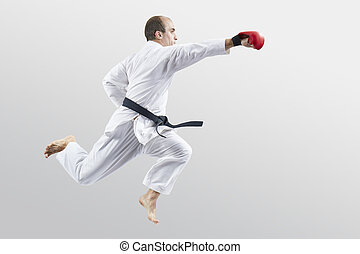 An adult athlete with red overlays on his hands beats with a hand in a jump