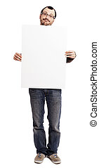 An adult caucasian man at his early 30's wearing casual sneakers, a pair of blue jeans and holding a large blank white sign. He's looking at the camera with a goofy expression. Isolated on white bac