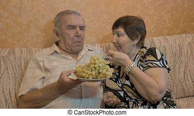 An adult couple eat grapes, and feed each other. close-up -...