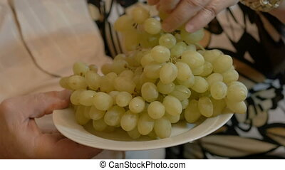 An adult couple eat grapes, and feed each other. close-up