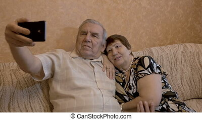 An adult couple makes selfie. They are sitting at home on the couch. Use a smartphone for photos