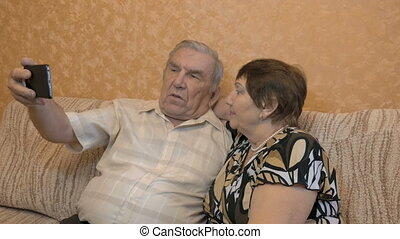 An adult couple makes selfie. They are sitting at home on the couch. Use a smartphone for photos. close-up