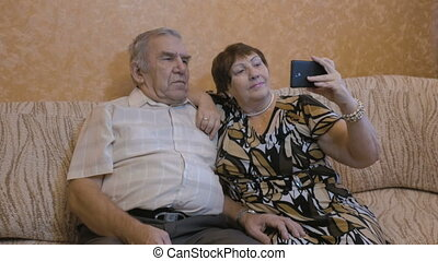 An adult couple makes selfie. Use a smartphone for photos