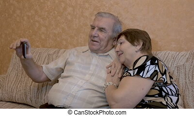 An adult couple makes selfie. Use a smartphone for photos close-up