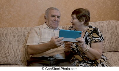An adult couple uses a tablet, they sit on the couch