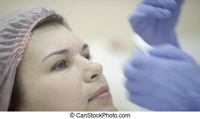An adult female patient woman in cap is injected botox with...