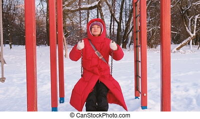 An adult girl in a red down jacket swinging on a red swing in the playground at sunset, slow motion