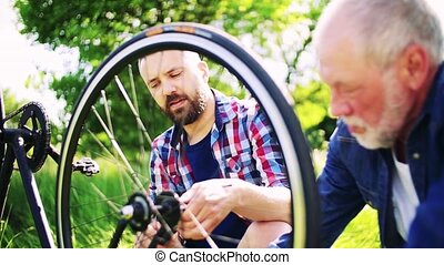An adult hipster son and senior father repairing bicycle...