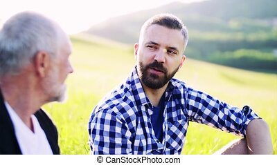 An adult hipster son and senior father sitting on the grass in nature, talking.