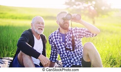 An adult hipster son and senior father with binoculars...