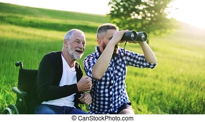 An adult hipster son with binoculars and senior father in...