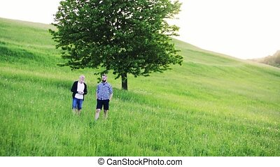 An adult hipster son with senior father on a walk in nature,...