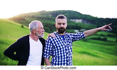 An adult hipster son with senior father standing in nature,...