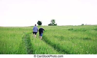 An adult hipster son with senior father walking in nature at...