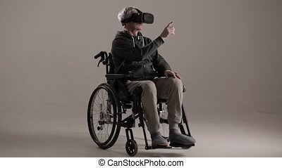An Adult in a Wheelchair Put on Virtual Reality Glasses. - A...