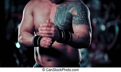An adult man bodybuilder binding his wrists. Mid shot
