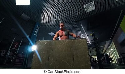 An adult man bodybuilder jumping on and off the cube in the gym. Mid shot