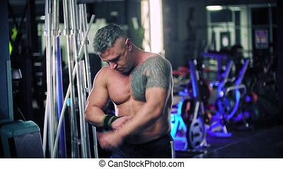 An adult man bodybuilder putting bandages on his wrists. Mid shot