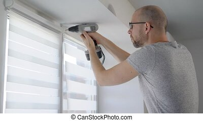 an adult man holds an electric drill in his hands and screws the window that protects him from light