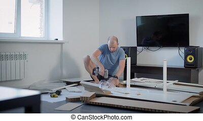 an adult man screws screws or bolts with a screwdriver to the base of the table, the person collects furniture in the living room near the TV set