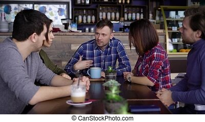 An adult man with short hair, dressed in a plaid shirt, tells his friends who sits with him at a wooden table about last week. The company drinks cappuccino and latte with milk