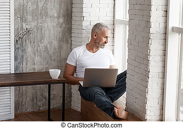 An adult man works at home on self-isolation, makes online orders, uses a coputer