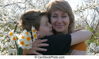 An adult middle-aged mother hugs and kisses her teenager's...