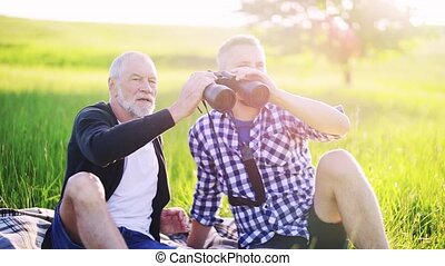 An adult son and senior father with binoculars sitting on...