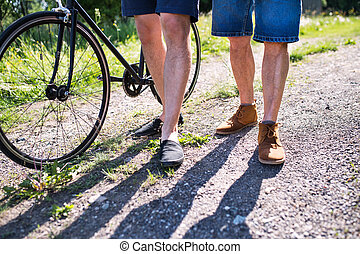 An adult son with bicycle and senior father walking on a road in sunny nature.