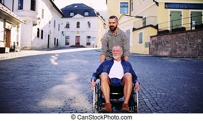 An adult son with senior father in wheelchair on a walk in small town.