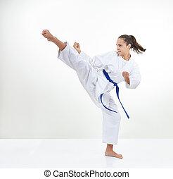 An adult sportswoman in karategi beats kick