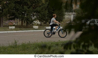 An adult woman in glasses rides a bicycle