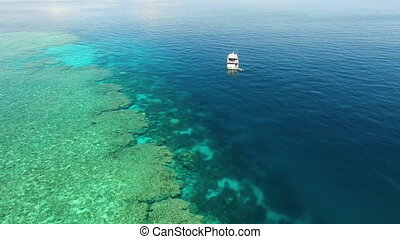 A drone shot of the great barrier reef and the blue ocean. The drone gets low as it shows a blue white ship from a far.