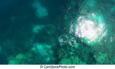 An aerial shot of a turquoise sea water