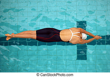 An aerial view of a female swimmer just off the starting blocks