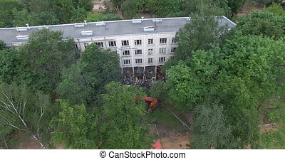 An aerial view of a half demolished building among green ...