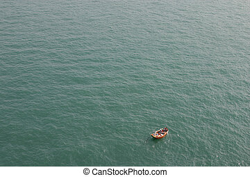 An aerial view of a small boat on a large expanse of calm open ocean.