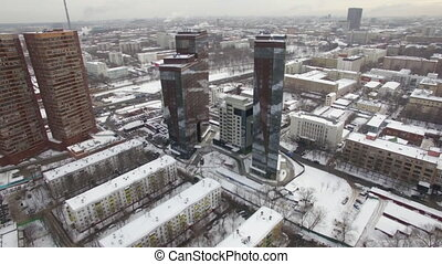 An aerial view of an urban landscape covered with snow. Two...