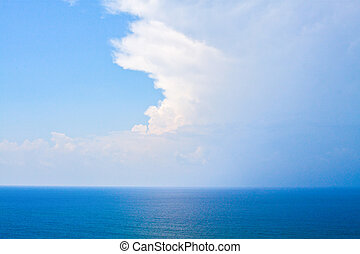 An aerial view of eternal blue sea or ocean with sunny and cloudy sky.