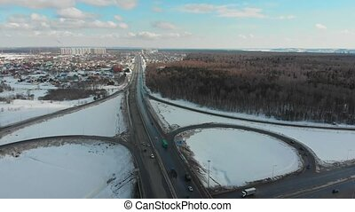 An aerial view on a highway at winter. Cars on the road....