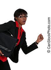 An African American businesswoman running.