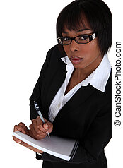 An African American businesswoman taking notes.