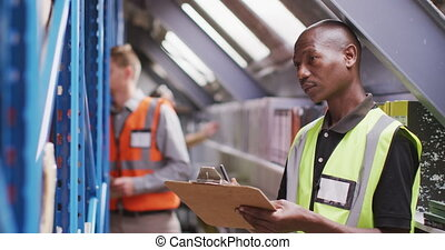 An African American male factory worker at a factory making hydraulic equipment taking notes
