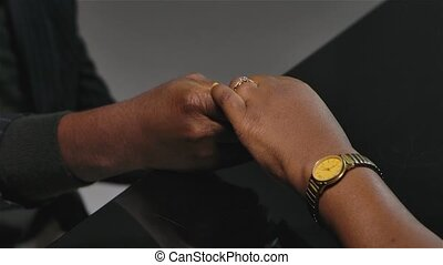 An African American man plays the grand piano and holds the hand of a woman with a gold watch. A ring sparkles on the woman's finger, close up. Slow motion.